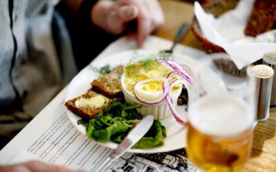 Karrysild med rugbrød og salat serveret med en fadøl