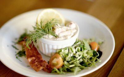 Skaldyrssalat med salat og bacon pyntet med persille